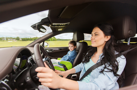 family, transport, road trip and people concept - happy woman with little daughter driving in car Stockfoto