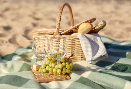 anniversary beach: food, holidays and celebration concept - close up of picnic basket with grapes, wine glasses, cheese and champagne bottle on summer beach