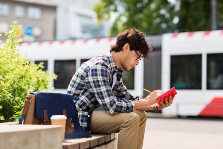 lifestyle, creativity, freelance, inspiration and people concept - creative man with notebook or diary writing sitting on city street bench Stock Photo
