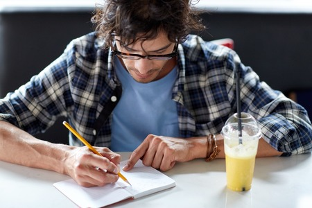 lifestyle, creativity, freelance, inspiration and people concept - creative man with notebook or diary writing and drinking juice at cafe Stock Photo
