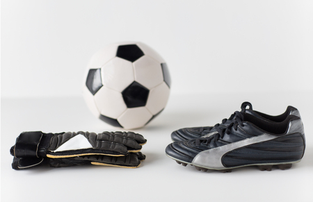 football shoes: sport, soccer, football and sports equipment concept - close up of ball, boots and goalkeeper gloves