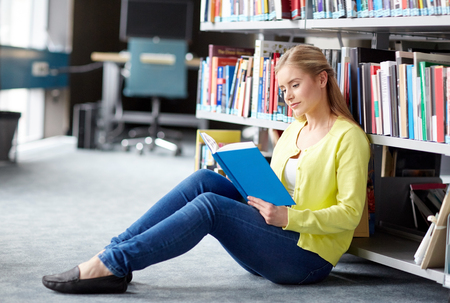 education, high school, university, learning and people concept - smiling student girl reading book sitting on floor at library