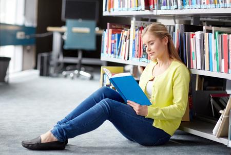 biblioteca: la educación, la escuela secundaria, la universidad, el aprendizaje y el concepto de la gente - chica estudiante libro sentado en el piso en la biblioteca leyendo sonriendo