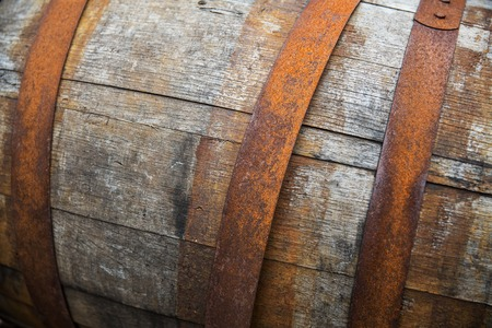 old container: storage, container and object concept - close up of old wooden barrel with rusty hoops outdoors