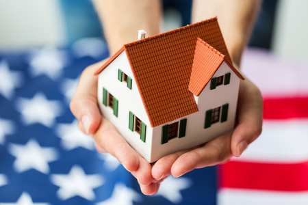 市民権、レジデンス、プロパティ、不動産、人々 の概念 - クローズ アップ両手リビングの家モデル アメリカの国旗