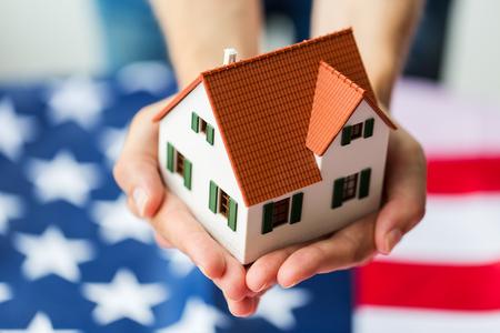 nacionalidad, residencia, propiedad, bienes raíces y concepto de la gente - cerca de las manos que sostienen viviendo modelo de casa sobre la bandera americana