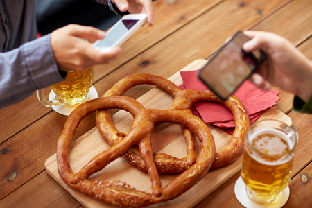 people, food, and technology concept - close up of hands with smartphone picturing beer and pretzel at bar or pub