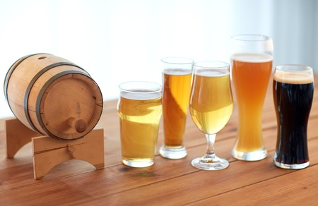 porter: brewery, drinks and alcohol concept - close up of different beers in glasses and barrel on table Stock Photo