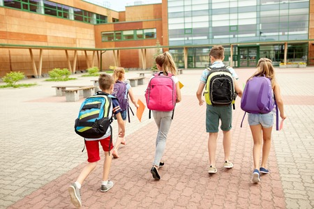 primary education, friendship, childhood and people concept - group of happy elementary school students with backpacks running outdoors Stock Photo