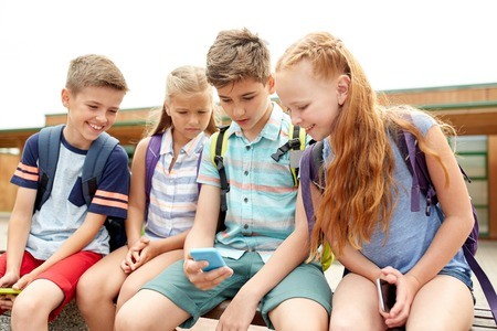 primary education, friendship, childhood, technology and people concept - group of happy elementary school students with smartphones and backpacks sitting on bench outdoors Stock Photo