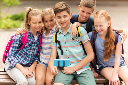 elementary: primary education, technology, friendship, childhood and people concept - group of happy school students with backpacks sitting on bench and taking picture by smartphone on selfie stick outdoors Stock Photo
