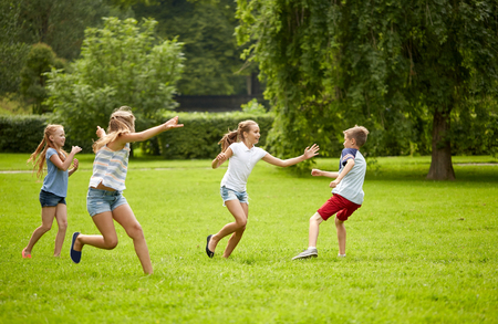 friendship, childhood, leisure and people concept - group of happy kids or friends playing catch-up game and running in summer park Foto de archivo
