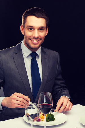 main course: restaurant, people and holiday concept - smiling man eating main course at restaurant Stock Photo