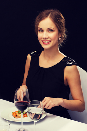 main course: restaurant, people and holiday concept - smiling young woman eating main course at restaurant