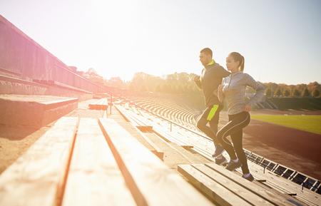 フィットネス、スポーツ、運動、ライフ スタイル コンセプト - スタジアムの 2 階を実行して幸せなカップル