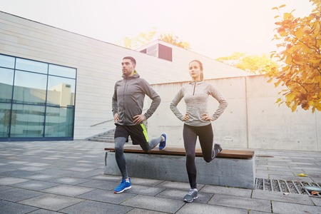 lunge: fitness, sport, people, exercising and lifestyle concept - couple doing lunge exercise on city street