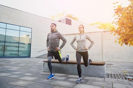 fitness, deporte, la gente, el ejercicio y el concepto de estilo de vida - pareja haciendo ejercicio estocada en la calle de la ciudad
