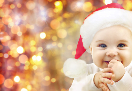 people, christmas, children and holidays concept - happy baby in santa hat over lights background photo