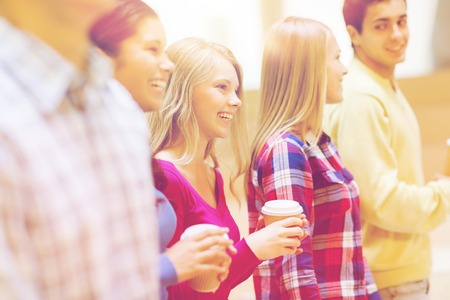education, high school, friendship, drinks and people concept - group of smiling students with paper coffee cups Imagens