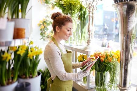 人、ビジネス、技術、販売、フローリスト ・ コンセプト - フラワー ショップでタブレット pc コンピューターと幸せな笑みを浮かべて花屋女
