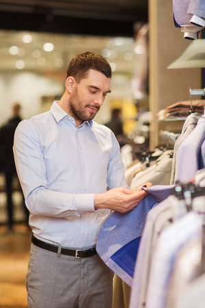 choosing: sale, shopping, fashion, style and people concept - elegant young man in shirt choosing clothes in mall or clothing store Stock Photo