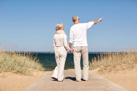 family, age, travel, tourism and people concept - happy senior couple holding hands and pointing finger on summer beach