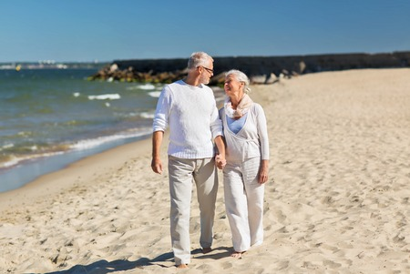 family, age, travel, tourism and people concept - happy senior couple holding hands and walking on summer beach