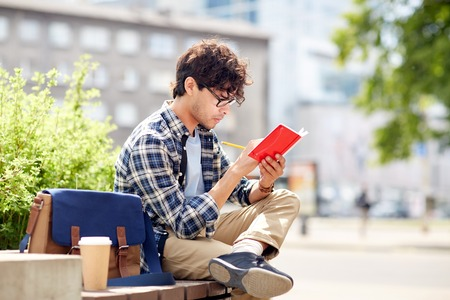 lifestyle, creativity, freelance, inspiration and people concept - creative man with notebook or diary writing sitting on city street bench Stock Photo - 64446215