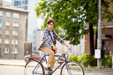 shoulder bag: people, style, leisure and lifestyle - young hipster man with shoulder bag riding fixed gear bike on city street Stock Photo
