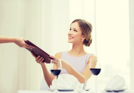 recieving: reastaurant and happiness concept - smiling young woman giving menu to waiter at restaurant