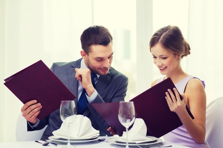 restaurant dining: restaurant, couple and holiday concept - smiling man looking into girlfriends or wifes menu at restaurant