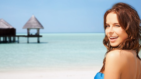 winking: travel, tourism, summer vacation and people concept - happy beautiful woman over tropical beach with bungalow background