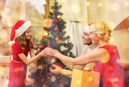 family, christmas, x-mas, happiness and people concept - smiling family in santa helper hats decorating christmas tree Stock Photo