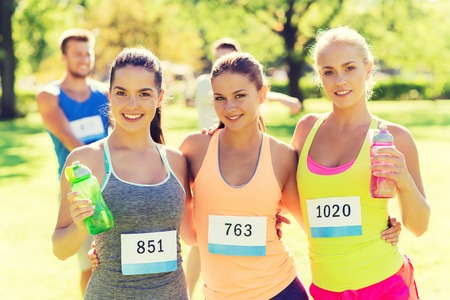 women friendship: fitness, sport, friendship, marathon and healthy lifestyle concept - happy young sporty women with racing badge numbers and water bottles outdoors Stock Photo