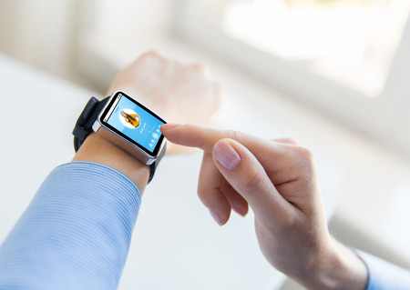 business, modern technology, media and people concept - close up of female hands setting smart watch with music player on screen at office Stock Photo