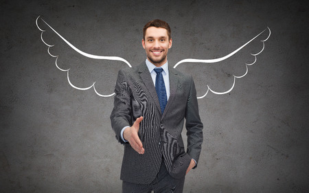 gestures: business, angel investor, safety, security and people concept - smiling young businessman with wings drawing giving hand for handshake over gray concrete background