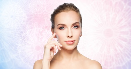 beauty, people and plastic surgery concept - beautiful young woman showing her cheekbone over rose quartz and serenity pattern background Stock Photo