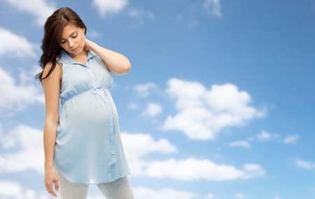 pregnancy, health, people and expectation concept - pregnant woman in bed touching her back and suffering from neckache over blue sky background Stock Photo