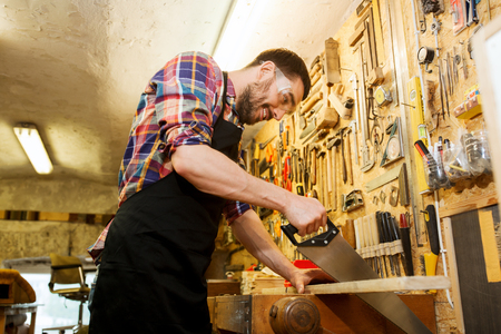 chippy: profession, carpentry, woodwork and people concept - happy smiling carpenter working with saw and wood plank at workshop