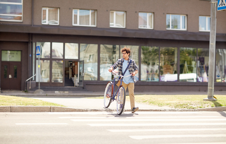 citylife: people, style, city life and lifestyle - young hipster man with shoulder bag and fixed gear bike crossing crosswalk on street Stock Photo