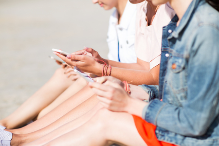 summer vacation, holidays, technology, travel and people concept - close up of young women with smartphones on beach