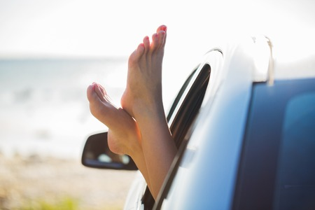 chiropody: summer vacation, holidays, travel, road trip and people concept - close up of young woman feet showing from car window Stock Photo