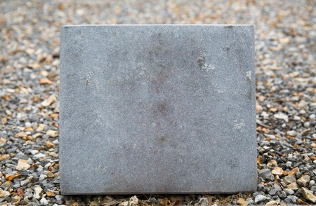 memorial plaque: grave and burial concept - close up of old cemetery gravestone or memorial stone plate