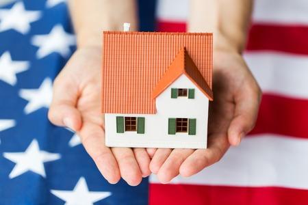 viviendas: nacionalidad, residencia, propiedad, bienes raíces y concepto de la gente - cerca de las manos que sostienen viviendo modelo de casa sobre la bandera americana
