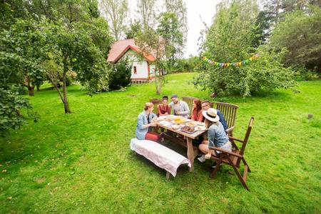 레저, 휴일, 먹고, 사람과 음식 개념 - 여름 정원 파티에서 저녁 식사를하는 행복 한 친구