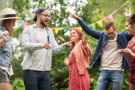 holiday gathering: leisure, holidays, fun and people concept - happy friends dancing at summer party in garden