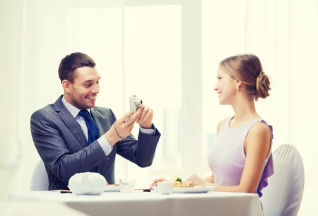 couple in love: restaurant, couple, technology and holiday concept - smiling man taking picture of wife or girlfriend with digital camera at restaurant