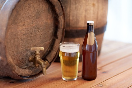 alehouse: brewery, drinks and alcohol concept - close up of old beer barrel, glass and bottle on wooden table