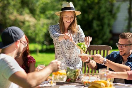 Freizeit, Urlaub, Essen, Menschen und Food-Konzept - glückliche Freunde beim Abendessen und Salat im Sommer Gartenparty teilen