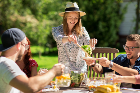 servings: leisure, holidays, eating, people and food concept - happy friends having dinner and sharing salad at summer garden party